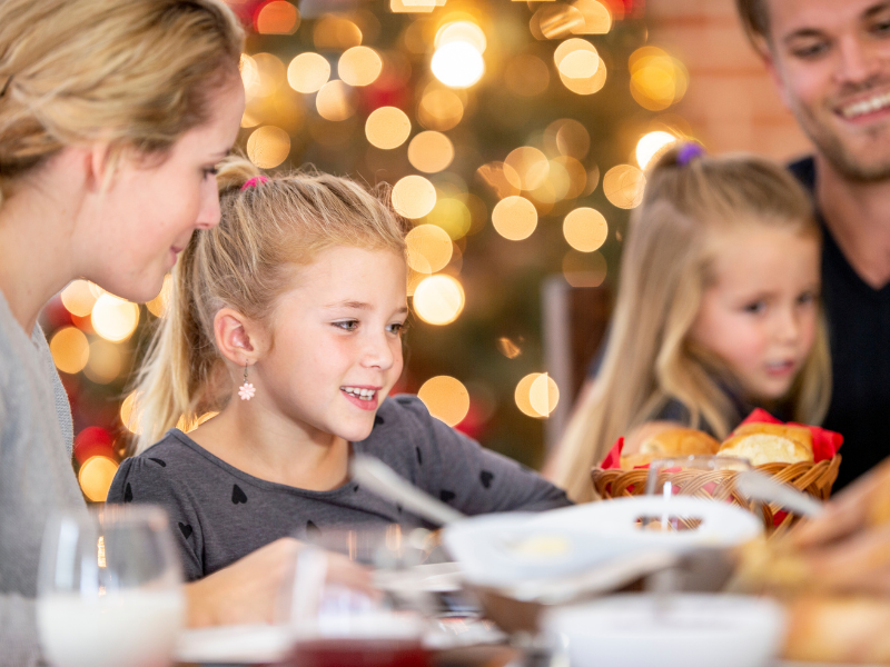 4 family members, 2 little girls and their parents, are eating holiday dinner with blurred holiday decorations in the background.